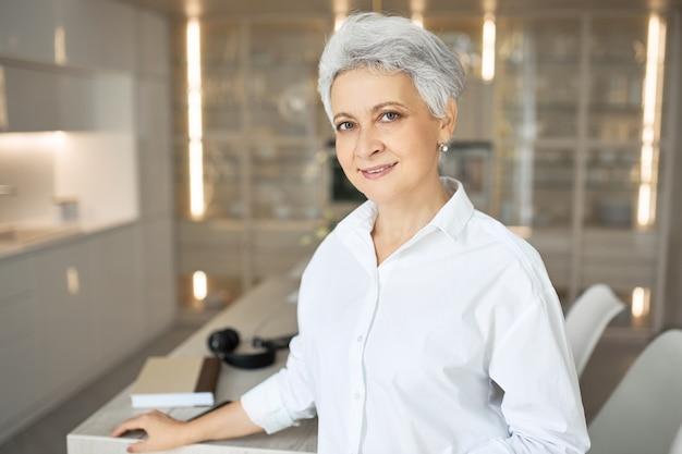 Modieuze grijze haren vrouwelijke makelaar in wit overhemd poseren binnenshuis. gelukkig stijlvolle vrouw manager permanent op kantoor tijdens werkdag