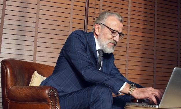 Modieuze grijze man, de eigenaar van het bedrijf zit aan een tafel en kijkt naar een laptop
