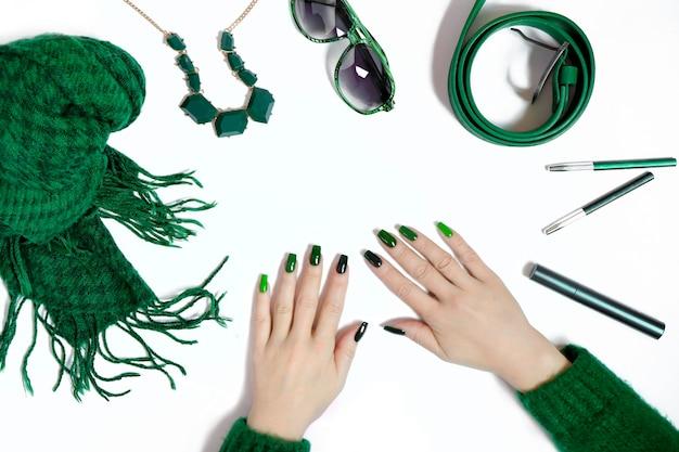 Modieuze groene manicure op lange nagels en damesaccessoires in verschillende tinten groen op een witte achtergrond.