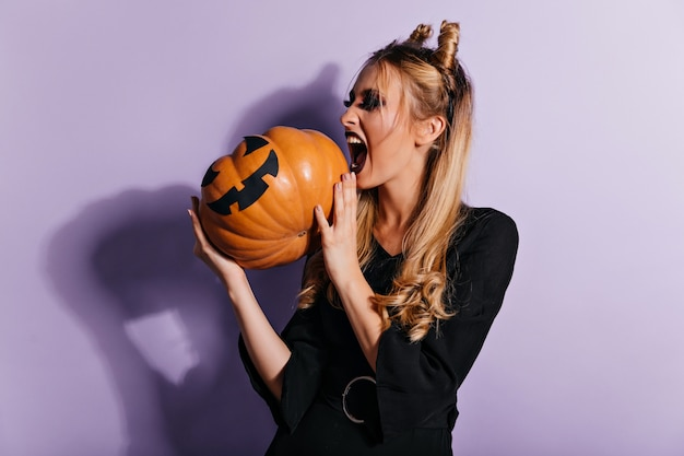 Modieuze heks die op paarse muur gilt. prachtig vampiermeisje dat pompoen bekijkt.