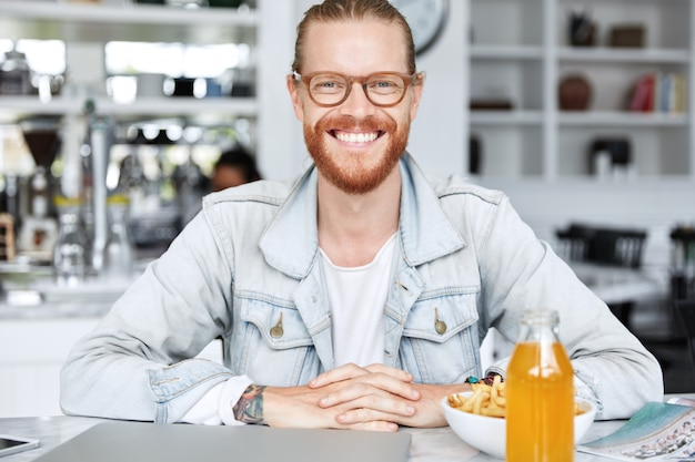 Modieuze hipster man gekleed in denim overhemd en stijlvolle bril