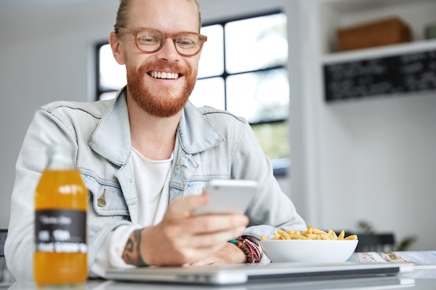 Modieuze hipster man gekleed in denim overhemd en stijlvolle bril