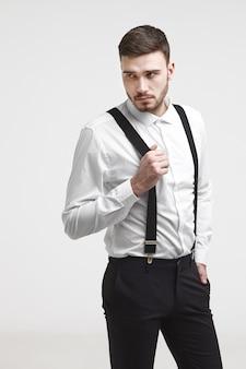 Modieuze hipster man met stoppels en stijlvol kapsel poseren voor lege studio muur, wegkijken met mysterieuze uitdrukking. knappe jonge bebaarde man gekleed in formele slijtage bretels trekken