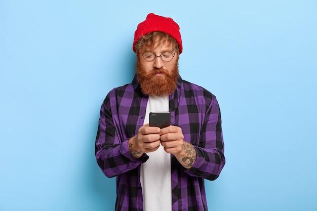 Modieuze hipster met rood haar en dikke baard, gefocust op smartphone, ontvangt een link naar een publicatie