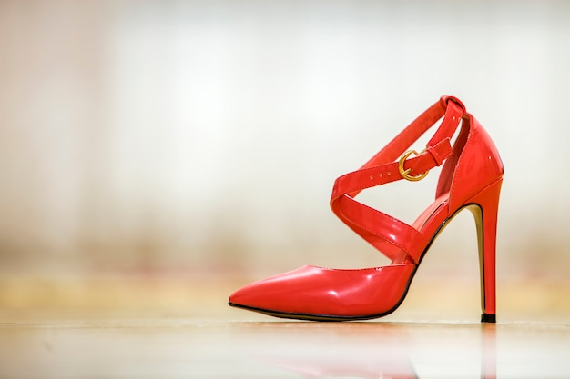 Modieuze hoge rode lederen rode uitgesneden vrouwelijke schoen met gouden gespen geïsoleerd