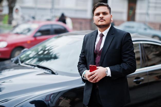 Modieuze indische zakenman in formele slijtage met mobiele telefoon die zich tegen zwarte bedrijfsauto op straat van stad bevinden.