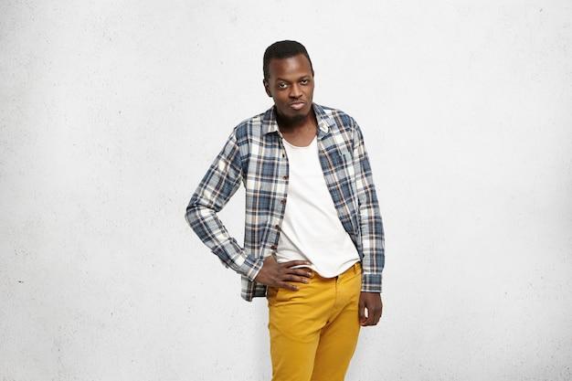 Modieuze jonge afro-amerikaanse man met mosterd-spijkerbroek en geruit hemd over een wit t-shirt met de hand op de heup, flirtende blik, lippen uitschietend alsof hij iemand probeert te verleiden