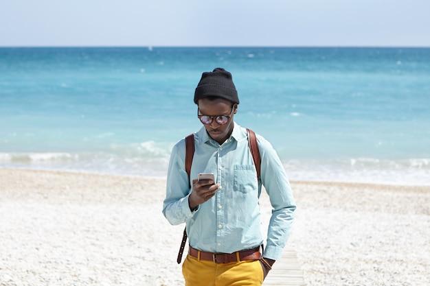 Modieuze jonge afro-amerikaanse mannelijke toerist met behulp van mobiele telefoon op woestijnstrand, het plaatsen van foto's van prachtig zeegezicht om hem heen via sociale media met azuurblauwe oceaan en blauwe lucht in horizon