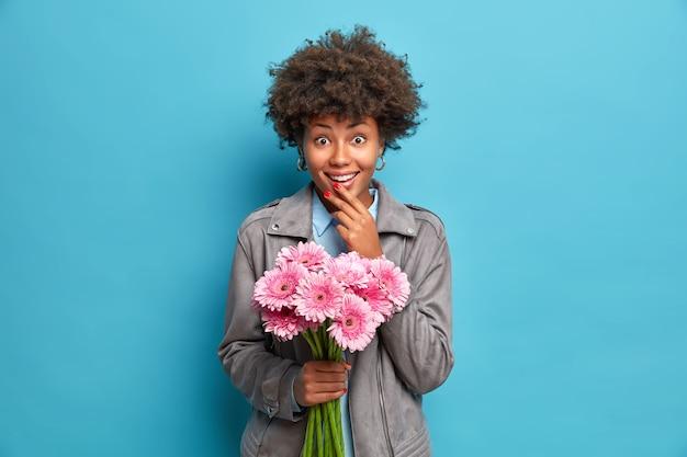 Modieuze jonge afro-amerikaanse vrouw ontvangt een boeket roze gerberabloemen van een liefhebbende boyfiend tijdens de date