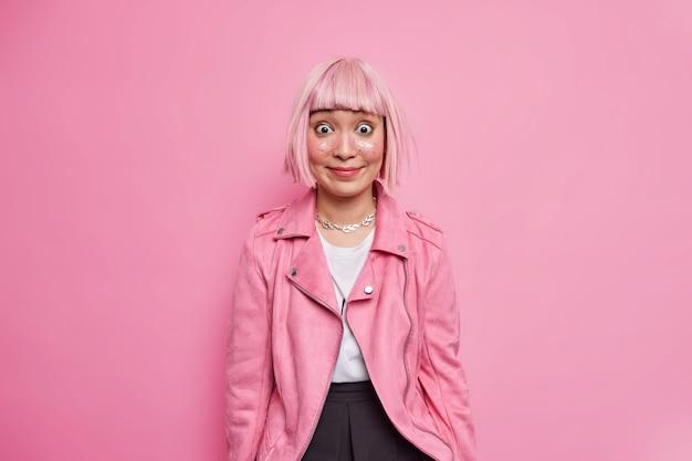 Modieuze jonge aziatische vrouw met bobkapsel ziet er blij en verrast uit, draagt make-up gekleed in stijlvolle kleding en bereidt zich voor op discofeest