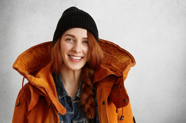 Modieuze jonge blanke vrouw in warme kleding poseren in studio