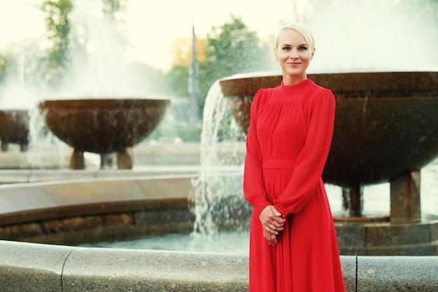 Modieuze jonge blonde vrouw die rode jurk draagt, zomerdag