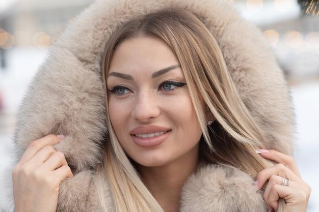 Modieuze jonge blonde vrouw in mode jas in de stad.