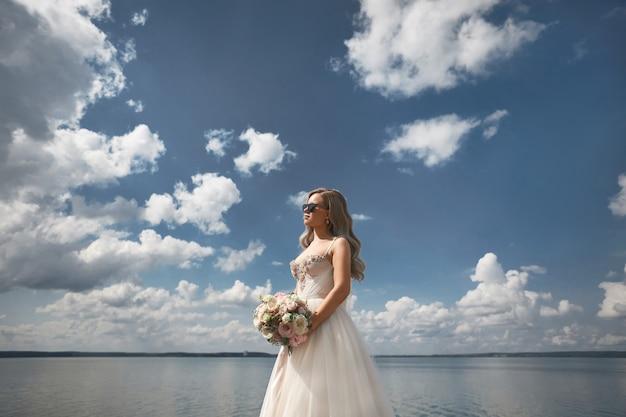 Modieuze jonge bruid met platina blond haar in trouwjurk poseren met boeket verse bloemen aan de zeekust.