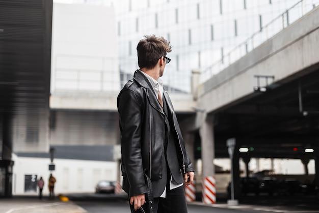 Modieuze jonge hipster in zonnebril in een oversized mode zwart leren jas voor jongeren met een stijlvol kapsel dat staat en terugkijkt in de buurt van een modern gebouw buitenshuis. trendy man op straat.