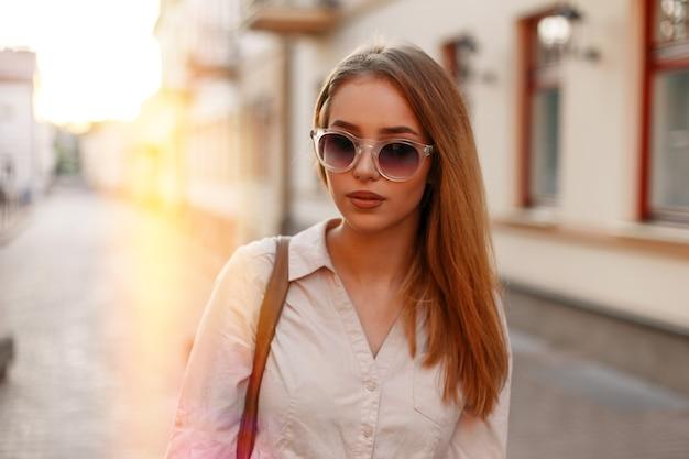 Modieuze jonge hipster vrouw in stijlvolle zonnebril in een modieuze witte jurk met een modieuze bruine leren tas loopt in de stad tegen de achtergrond van oranje schittering van de zon. een meid met stijl.