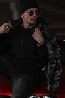 Modieuze jonge knappe hipster man met stijl zonnebril met zwarte jas, pullover met hoed zit in de buurt van een rode auto op straat