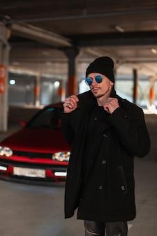 Modieuze jonge knappe man in coole zonnebril in een elegante zwarte jas met een hoed op straat tegen de achtergrond van een rode auto