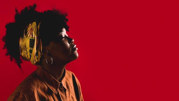 Modieuze jonge krullende afrikaanse amerikaanse vrouw in studio met gekleurde achtergrond