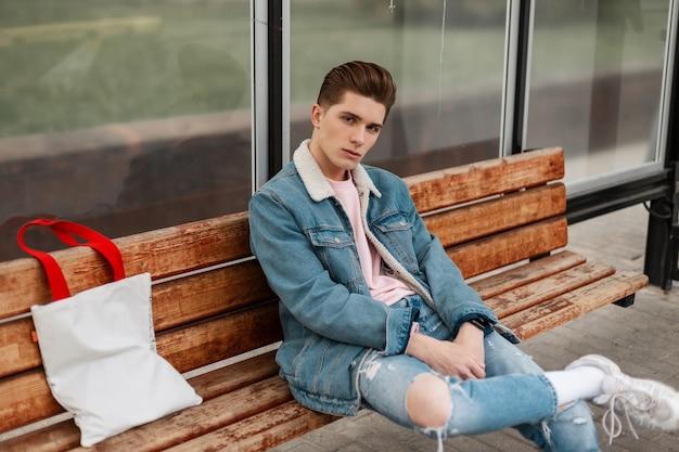 Modieuze jonge man in casual spijkerbroek kleding in trendy witte sneakers met vintage stoffen tas zit op houten bankje bij een bushalte in de stad. knappe jongen in stijlvolle denim jeugdkleren op straat.