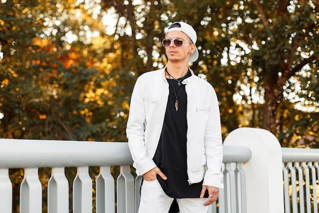 Modieuze jonge man in een stijlvolle witte jas met zonnebril in het park