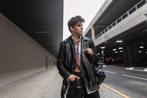 Modieuze jonge man in een trendy leren zwarte jas in een shirt in broek met een stijlvolle rugzak met een kapsel poseren in de buurt van de weg in de stad. europese man mannequin in vrijetijdskleding voor de jeugd.