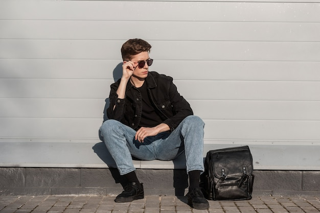 Modieuze jonge man in vintage zonnebril in stijlvolle casual denim kleding voor jongeren in sneakers