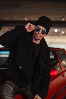Modieuze jonge man met coole zonnebril in een elegante zwarte jas met een hoed zit in de buurt van een rode auto in de stad