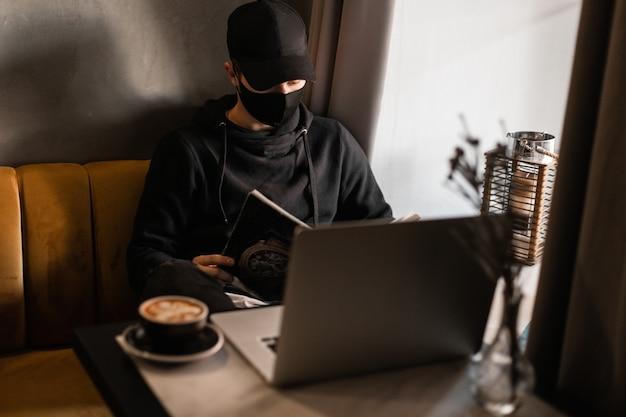 Modieuze jonge man met een beschermend masker en zwarte hoed met een stijlvolle hoodie zit en leest een tijdschrift in een café met een laptop en koffie