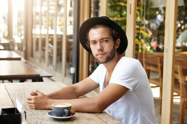 Modieuze jonge man met stoppels met vreugdevolle blik, zittend aan houten tafel in de coffeeshop buiten met kopje cappuccino voor hem