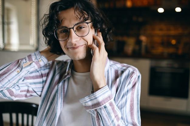 Modieuze jonge man met zwarte krullen glimlachend in de camera tijdens het bellen.