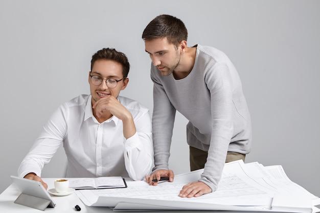 Modieuze jonge mannelijke architecten die samen aan nieuw woonproject werken, tekeningen controleren en digitale tablet gebruiken