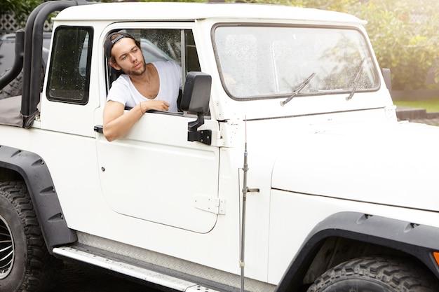 Modieuze jonge mens die zijn wit voertuig met vierwielaandrijving drijven