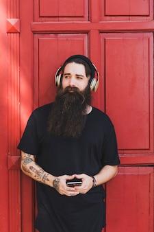 Modieuze jonge mens het luisteren muziek op hoofdtelefoons tegen rode deur