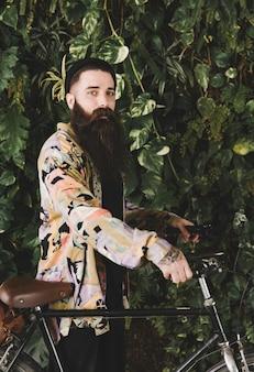 Modieuze jonge mens met zijn fiets die zich voor installatie bevindt