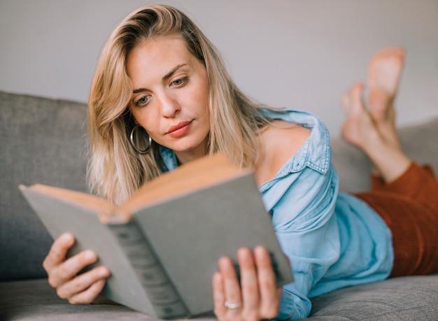 Modieuze jonge mooie vrouw die op bank ligt die het boek leest