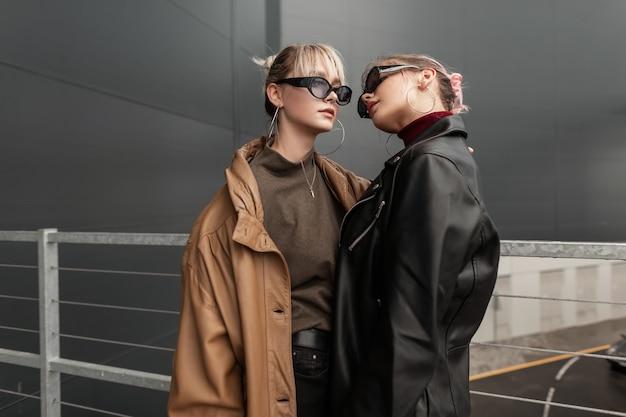 Modieuze jonge paar mooie meisjes met zonnebril in mode lederen jas op straat in de buurt van een modern gebouw