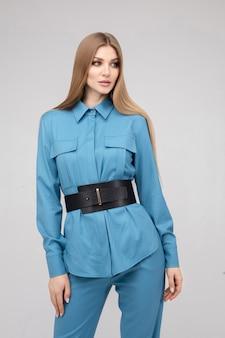 Modieuze jonge stijlvolle vrouw poseren in blauwe broekpak met zwarte riem middellange afstandsschot. trendy modieuze vrouw die stijlvolle casual kleding draagt, geïsoleerd op een witte studioachtergrond