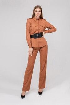 Modieuze jonge stijlvolle vrouw poseren in broekpak met zwarte riem middellange afstand schot. trendy modieuze vrouw die stijlvolle casual kleding draagt, geïsoleerd op een witte studioachtergrond
