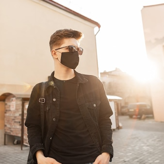 Modieuze jonge tiener man in zonnebril in zwarte stijlvolle jeans kleding loopt buiten bij zonsondergang