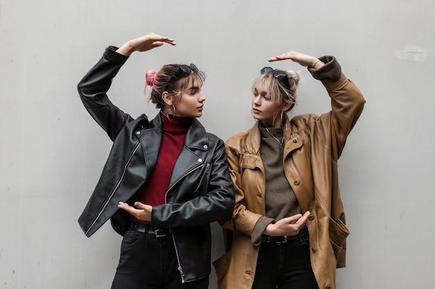 Modieuze jonge twee vriendinnen meisjes met in coole leren jas poseren in de buurt van een grijze muur op straat