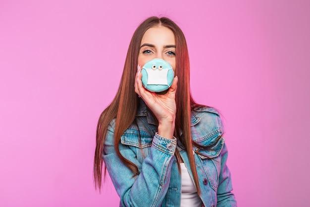 Modieuze jonge vrouw behandelt gezicht met grappige doughnut in medisch masker