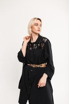 Modieuze jonge vrouw blonde in elegante lange zwarte jurk staande binnenshuis in de buurt van vintage witte muur binnenshuis. stijlvolle mannequin modern meisje poseren. retro stijl. dameskleding voor dames