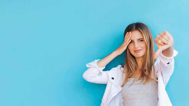 Modieuze jonge vrouw die duimen tonen neer tegen blauwe achtergrond