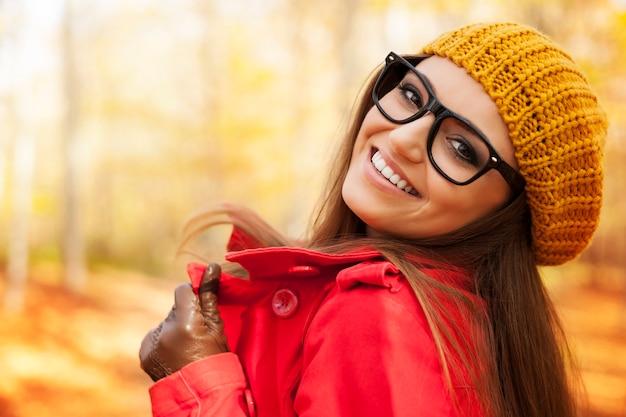 Modieuze jonge vrouw die in de herfstseizoen genieten van