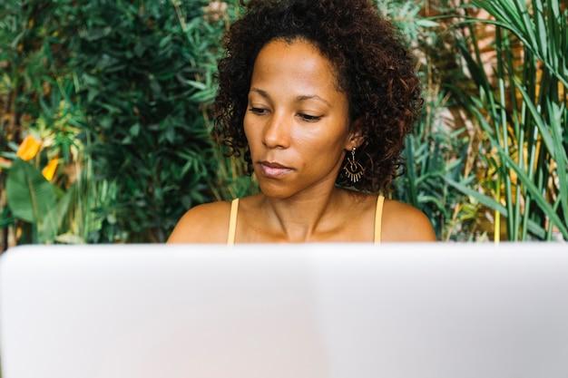 Modieuze jonge vrouw die laptop bekijkt