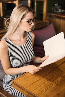 Modieuze jonge vrouw die menu's in het restaurant controleert