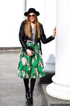 Modieuze jonge vrouw die op straat loopt met leren jas en bloemenrok