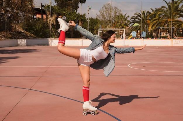 Modieuze jonge vrouw die rolschaats draagt die zich op één been over het voetbalhof bevindt