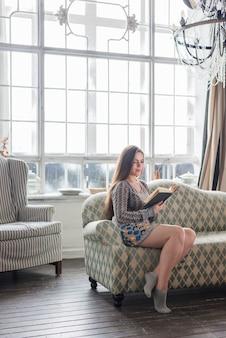 Modieuze jonge vrouw die sokken draagt die boek thuis lezen